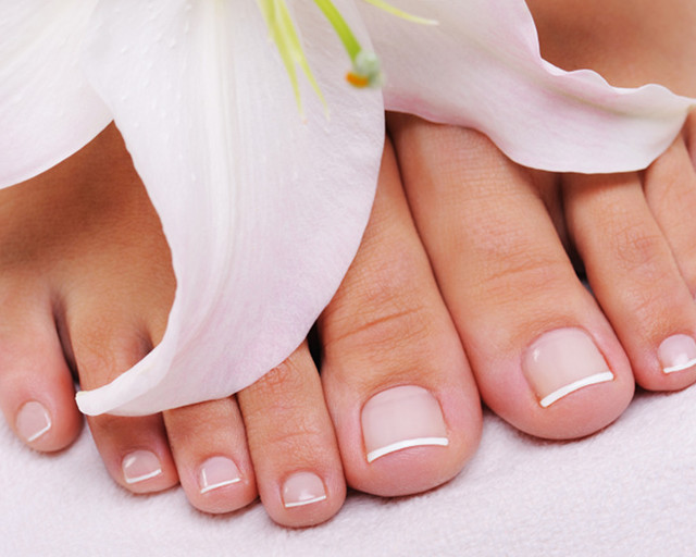 Beautiful well-groomed female feet with the French pedicure and flower